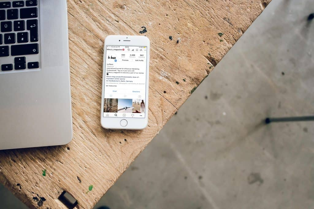 White smartphone on desk showing Instagram account.